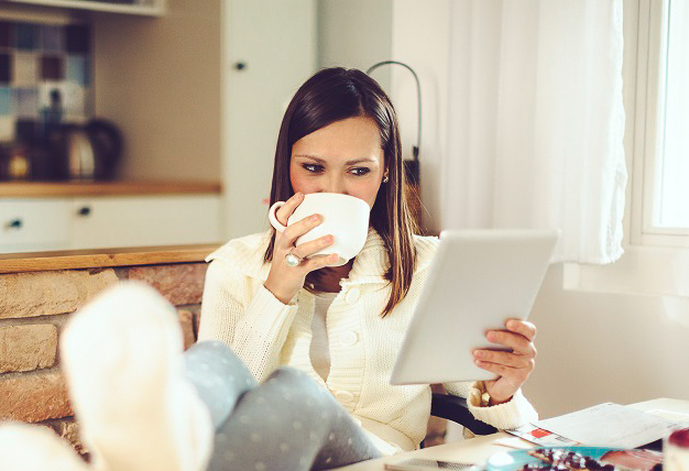 Woman drinking coffee while looking at a tablet.